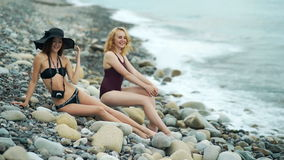 Two beautiful woman relaxed and enjoyed over the sea sitting on the big wild stone beach stock video footage