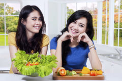 Two beautiful woman shows healthy food Royalty Free Stock Photo