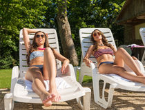 Two beautiful woman sunbathing on the beach Stock Photos