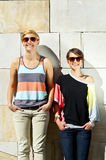 Two  beautiful woman with sunglasses on stone wall background Stock Images