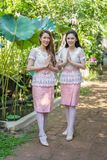 Two beautiful woman in Thai traditional dress is pay respect. Two beautiful young women in Thai traditional dress is pay respect royalty free stock photo