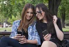 Two beautiful woman typing on the smart phone in a park Stock Images