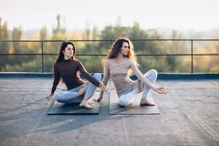 Two beautiful women doing yoga asana virabhadrasana on the roof Royalty Free Stock Photo