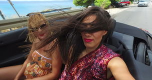 Two beautiful women at the back of convertible enjoying windy ride. Two attractive female friends riding in the back seat of convertible with wind in their hair stock footage