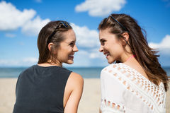 Two beautiful women on beach looking at each other laughing stock photography
