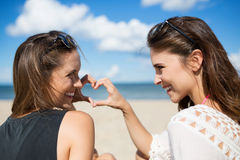 Two beautiful women on beach making heart shape laughing royalty free stock image