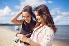 Two beautiful women on beach watching photos on camera royalty free stock images