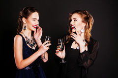 Two beautiful women in  black cocktail dresses. Two beautiful women in elegant black cocktail dresses celebrating with champagne standing  raising their glasses Royalty Free Stock Photography