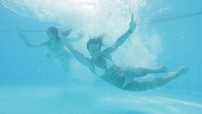 Two beautiful women blonde and brunette having fun in the swimming pool. Fabulous slim female swimmers in white bikinis dive and enjoy their lives, while being stock footage