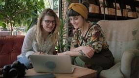 Business presentation and friend talks in cafe shop. Two beautiful women, brunette and blonde, digital natives, millennial hipsters use video chat application on stock video