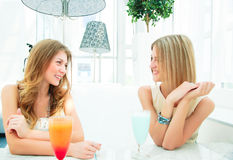 Two beautiful women chatting in a cafe Stock Images