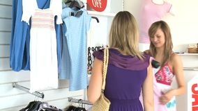 Two beautiful women choosing clothes. Standing in a clothes store stock video