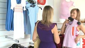 Two beautiful women choosing clothes stock video