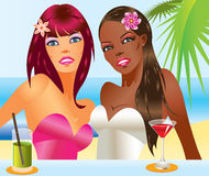 Two beautiful women with cocktails on the beach Royalty Free Stock Photo