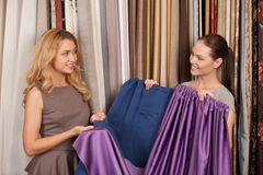 Two beautiful women comparing textile. Stock Photography