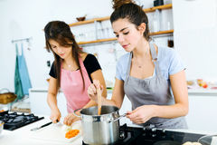 Two beautiful women cutting and cooking fresh vegetables in kitchen. Portrait of two beautiful women cutting and cooking fresh vegetables in kitchen Stock Images