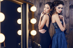 Two beautiful women with dark hair in luxurious dresses. Fashion studio photo of two beautiful sensual women with dark hair in luxurious dresses with bijou Stock Images