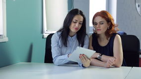 Two beautiful women discuss different ideas at office. Charming brunette at the left side is dressed in blue cotton shirt with daily make-up and bright red stock footage