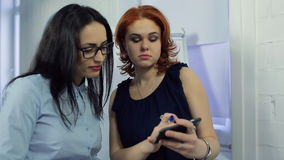 Two beautiful women discuss important information at office. On the right ginger woman is dressed in darkly blue chiffon blouse. She holds mobile phone in hand stock footage