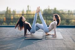 Two beautiful women doing acroyoga asana on the roof outdoors. A synchronous pose of a triangle with a hold on hands. Flexibility, strength, beauty stock photography