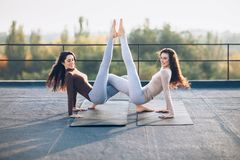 Two beautiful women doing acroyoga asana on the roof outdoors Stock Images