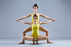 Two beautiful women doing partner yoga asana. Two young beautiful women doing partner yoga asana royalty free stock photo