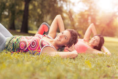 Exercising In Nature. Two beautiful women doing sit-ups exercise in the park. Selective focus Stock Images