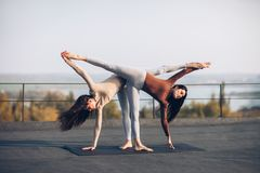 Two beautiful women doing yoga asana Ardha Chandrasana. On the roof outdoors. Half Moon Pose stock images