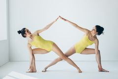 Two beautiful women doing yoga asana extended side angle pose. Two young beautiful women doing yoga asana extended side angle pose Utthita Parsvakonasana stock photos