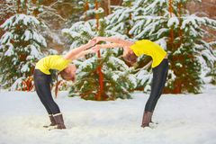 Two beautiful women doing yoga outdoors in snow. Two beautiful women doing yoga outdoors in the snow Royalty Free Stock Photography