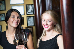 Two beautiful women drinking champagne on a bar counter Royalty Free Stock Photos