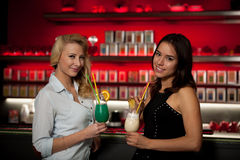 Two beautiful women drinking cocktail in a night club and having Royalty Free Stock Photography