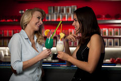 Two beautiful women drinking cocktail in a night club and having Royalty Free Stock Image