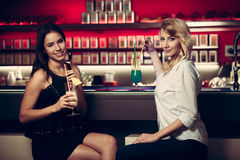 Two beautiful women drinking cocktail in a night club and having Stock Images