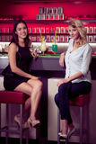 Two beautiful women drinking cocktail in a night club and having. Two beautiful women drinking cocktail in a night club Stock Photo