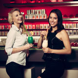 Two beautiful women drinking cocktail in a night club and having Royalty Free Stock Photo