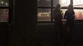 Two beautiful women drinking cocktails, browsing on smartphones at nightclub. Stock footage stock footage
