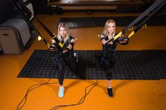 Two beautiful woman in Electrical Muscular Stimulation suit doing squat exercise for back and with suspension. Two beautiful women in Electrical Muscular royalty free stock image