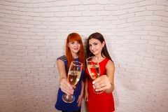 Two beautiful women in evening wear clinking glasses of champagn royalty free stock photography