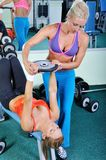Two beautiful women exercise in gym with weights Royalty Free Stock Image