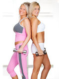 Two beautiful women in fitness outfit. Using weights stock photos