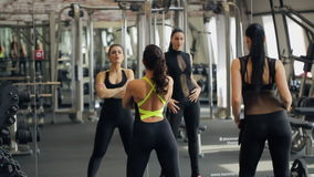 Two beautiful women flaunt in front of mirror in gym. stock footage