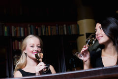 Two beautiful women friends drinking champagne on a bar counter. Two beautiful elegant women friends in stylish simple black cocktail dresses drinking a glass of Royalty Free Stock Photography