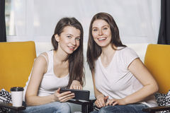 Two beautiful women friends talking happy smiles among. The books at home Stock Photos