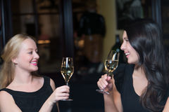Two beautiful women friends toasting each other. Two beautiful elegant women friends in stylish simple black cocktail dresses toasting each other with glasses of Royalty Free Stock Images