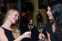 Two beautiful women friends toasting each other. Two beautiful elegant women friends in stylish simple black cocktail dresses toasting each other with glasses of Royalty Free Stock Image
