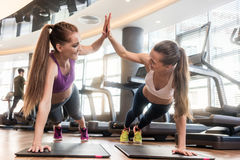 Two beautiful women giving high five while practicing basic plan. Two young and determined beautiful women giving high five while practicing basic plank exercise Stock Photos