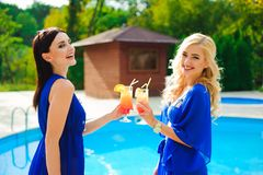 Two beautiful women having cocktails together by the swimming pool. stock images