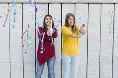 Young woman having fun with confetti over yellow background. Two beautiful women having fun outdoors with confetti. Celebration concept. Lifestyle royalty free stock photo