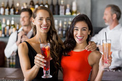 Two beautiful women holding cocktail glass. In restaurant Stock Photo